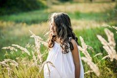 La bella ragazza del bambino con capelli biondi lunghi viaggia nel campo giallo variopinto Fotografie Stock