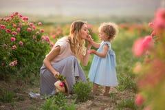 La bella ragazza del bambino delle coppie con la madre sta camminando nel giardino con i fiori rosa delle rose del fiore, tempo d immagini stock libere da diritti