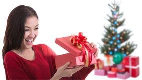La bella ragazza dell'Asia con natale del regalo ha decorato il fondo Immagine Stock