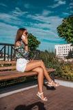 La bella ragazza dell'estate in parco si siede su un banco in aria fresca Nelle mani del telefono, delle chiamate e dei colloqui, immagini stock libere da diritti