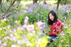 La bella ragazza della donna della natura cinese asiatica sveglia felice in un parco della molla gode del libro colto tempo liber Immagine Stock