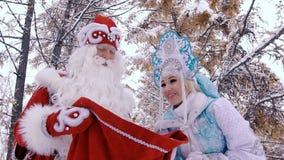 La bella ragazza della neve è eccitata per esaminare il padre che Frost è borsa con i regali video d archivio