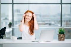 La bella ragazza della testarossa lavora al computer portatile e ad esaminare la macchina fotografica Fotografia Stock Libera da Diritti