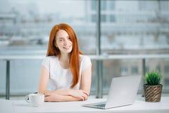 La bella ragazza della testarossa lavora al computer portatile e ad esaminare la macchina fotografica Fotografia Stock
