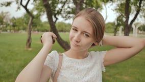 La bella ragazza dello studente, sorridente, pettina i suoi capelli lunghi nel parco Resto durante lo studio video d archivio