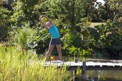 La bella ragazza di forma fisica con lo sport dell'estate mette l'allungamento in cortocircuito lei armi Immagine Stock