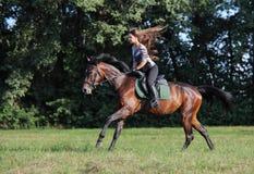 La bella ragazza di modello sexy monta un cavallo in prato al tramonto fotografia stock