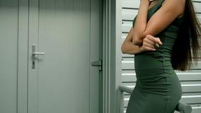 La bella ragazza di modo in vestito sexy sta su una via vicino alla porta stock footage