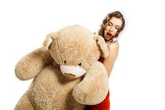 La bella ragazza di natale che abbraccia il grande giocattolo ha isolato il fondo bianco Fotografia Stock
