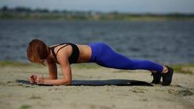 La bella ragazza di sport fa un esercizio della plancia sulla riva del lago blu stock footage