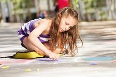 La bella ragazza disegna con gesso sulla via Immagini Stock Libere da Diritti