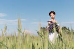 La bella ragazza dolce con i capelli dell'intrecciatura nelle prendisole bianche dell'estate che cammina in un campo con un mazzo Immagini Stock