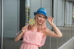 La bella ragazza ed in un cappello blu tiene la caramella del caramello in Th Fotografia Stock