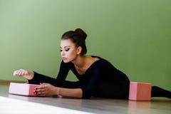 La bella ragazza elegante del ballerino di balletto moderno con l'ente perfetto si siede sul pavimento sopra su cordicella Immagini Stock
