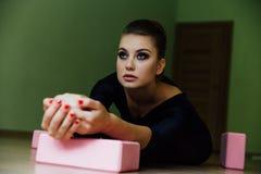 La bella ragazza elegante del ballerino di balletto moderno con l'ente perfetto si siede sul pavimento sopra su cordicella Immagini Stock Libere da Diritti
