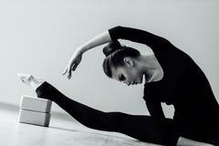 La bella ragazza elegante del ballerino di balletto moderno con l'ente perfetto si siede sul pavimento sopra su cordicella Fotografie Stock