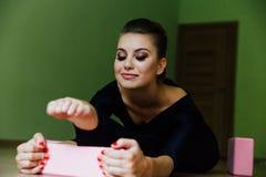 La bella ragazza elegante del ballerino di balletto moderno con l'ente perfetto si siede sul pavimento sopra su cordicella Fotografie Stock Libere da Diritti