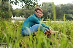 La bella ragazza emozionale si siede su un lago fra l'erba e il wate Fotografia Stock Libera da Diritti