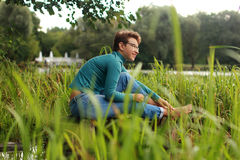 La bella ragazza emozionale si siede su un lago fra l'erba e il wate Fotografie Stock