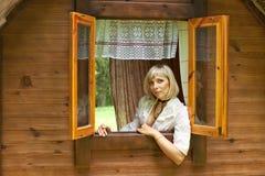 La bella ragazza europea osserva fuori la finestra Immagine Stock Libera da Diritti