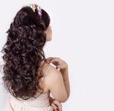 La bella ragazza fa i suoi riccioli dei capelli su capelli neri lunghi decorati con una corona dei fiori Fotografia Stock