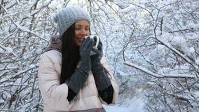 La bella ragazza felice si scalda con tè caldo neve archivi video