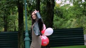 La bella ragazza felice sta stando sulla via con i palloni archivi video