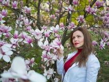 La bella ragazza fra l'albero sping del fiore di rosa della magnolia fiorisce Immagine Stock