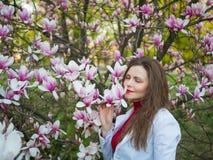 La bella ragazza fra l'albero sping del fiore di rosa della magnolia fiorisce Immagini Stock Libere da Diritti