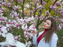 La bella ragazza fra l'albero sping del fiore di rosa della magnolia fiorisce Fotografia Stock