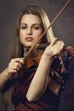 La bella ragazza gioca le fiddle Fotografie Stock Libere da Diritti