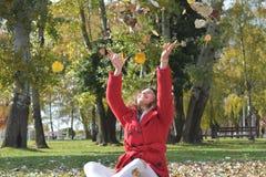 La bella ragazza gode dell'autunno Fogli di lancio Immagini Stock Libere da Diritti