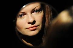 La bella ragazza guarda in specchio e fa il trucco Fotografie Stock Libere da Diritti