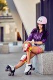 La bella ragazza inserisce sopra l'ingranaggio protettivo per rollerblading fotografie stock libere da diritti