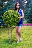 La bella ragazza integrale in parco vicino ai cespugli decorativi Fotografia Stock Libera da Diritti