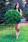 La bella ragazza integrale in parco vicino ai cespugli decorativi Fotografia Stock