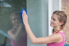 La bella ragazza lava una finestra in una casa con mattoni a vista Fotografie Stock Libere da Diritti