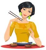 La bella ragazza mangia con i bastoncini Fotografie Stock
