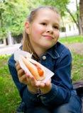 La bella ragazza mangia il hot dog Immagini Stock