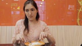 La bella ragazza mangia un pancake con il gelato in caffè stock footage
