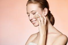 La bella ragazza massaggia il fronte sfrega e sorrisi Immagini Stock Libere da Diritti