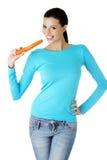 La bella ragazza morde le carote su bianco Immagini Stock Libere da Diritti