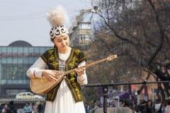 La bella ragazza nel costume kazako nazionale gioca il dombra piega dello strumento musicale sul immagini stock