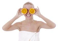 La bella ragazza nel salone della stazione termale tiene due metà delle arance nella e Immagine Stock Libera da Diritti