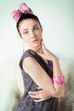 La bella ragazza nell'immagine retro con un arco rosa con bello trucco sta sedendosi su una sedia nello studio su un fondo blu Fotografia Stock