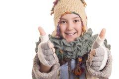 La bella ragazza nell'inverno caldo copre la mostra dei pollici su Fotografie Stock
