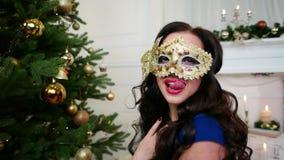 La bella ragazza nella maschera che celebra il nuovo anno, Natale si maschera, partito vicino all'albero di Natale, una giovane d stock footage