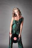 La bella ragazza nella tendenza copre con il disco del vinile. Immagine Stock