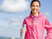 La bella ragazza nello sport copre l'acqua potabile dopo l'allenamento sulla spiaggia Fotografie Stock