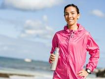 La bella ragazza nello sport copre l'acqua potabile dopo l'allenamento sulla spiaggia Fotografie Stock Libere da Diritti